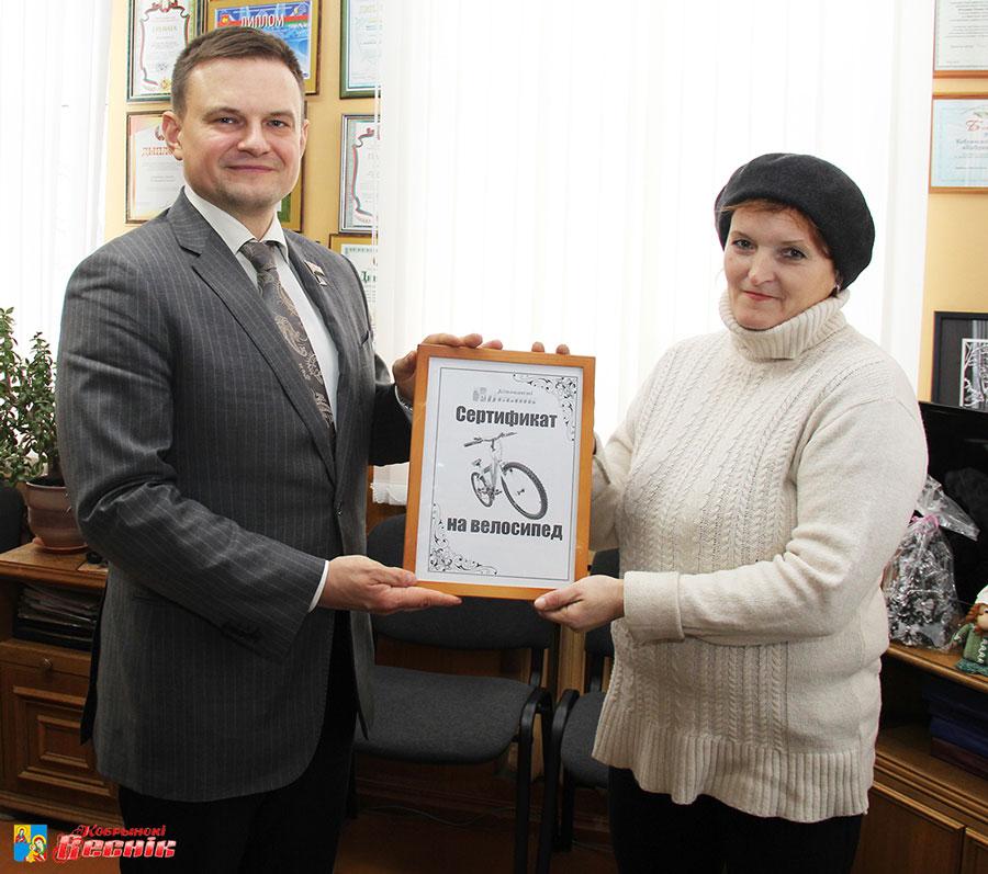 редактор газеты «Кобрынскі веснік»  Роман Мельник вручает подарочный сертификат Людмиле Денисюк