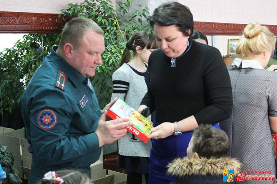 Николай Кузьмицкий и директор детского дома Наталия Дудко вручают подарки воспитанникам детского дома